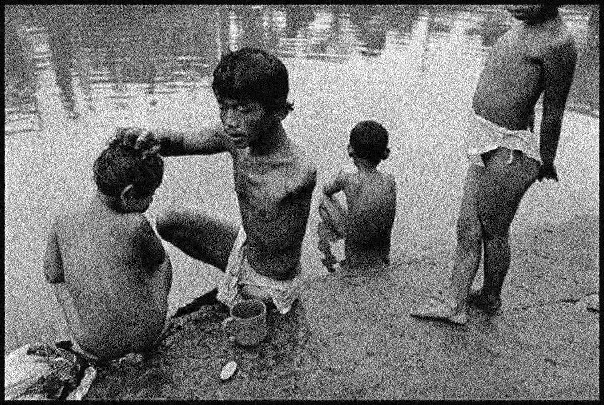 3-یک فرد معلول فرزندانش را با آب آلوده کانال می شوید. 1998، اندونزی، جیمز نچوی