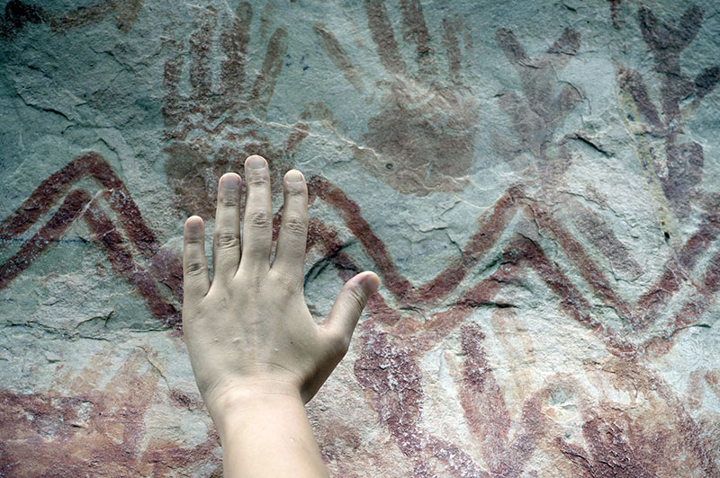 Palaeo-anthropologist Ella Al-Shamahi compares her hand to a handprint created around 12,000 years ago at Cerro Azul in Guaviare state, Columbia. Photo by Marie-Claire Thomas, courtesy Wild Blue Media.